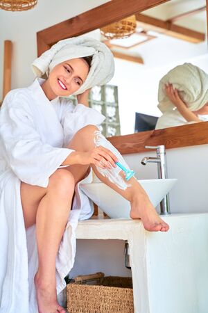 Photo of cheerful woman shaving her legs in bathroom. 스톡 콘텐츠