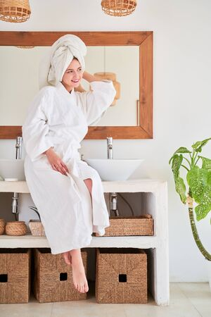 Full-length image of young woman in white bathrobe and with towel on her head sitting on sink.
