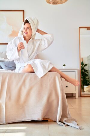 Image of girl in white bathrobe with mug of coffee in her hands lying on bed.