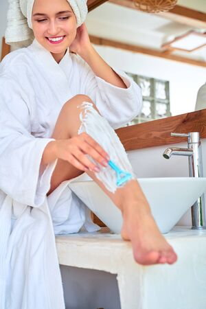 Image of smiling woman in white coat shaving her legs in bath