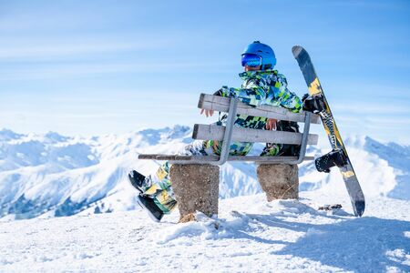 Photo of athlete sitting on bench with snowboard at winter resort in afternoon Reklamní fotografie