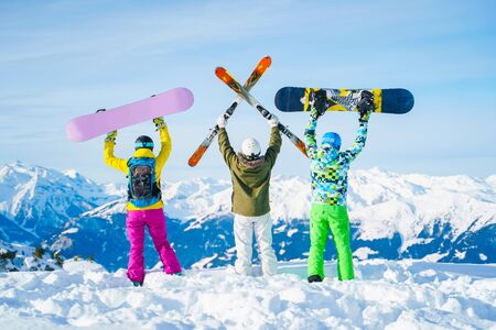 Photo from behind of three athletes with arms raised with snowboards and skis on day at winter resort 版權商用圖片