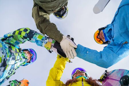Bottom photo of young snowboarders doing handshake on blue sky background
