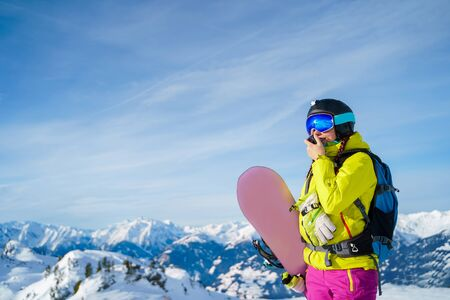 Athletic woman in helmet and mask with walkie-talkie and snowboard standing on snowy slope on winter day