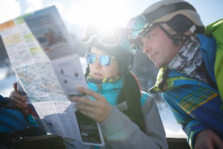Photo of woman and man tourists with map in hands at snow resort.