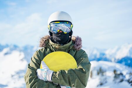 Portrait of man in helmet with snowboard standing on snow resort on winter day