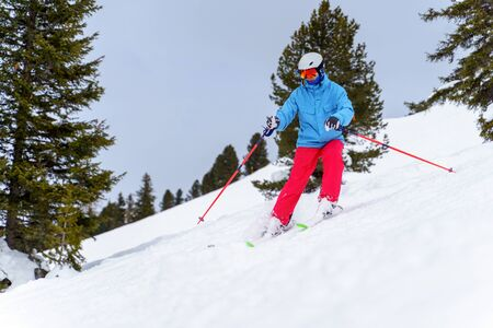 Photo of sports man in helmet skiing in winter resort from snowy slope with trees