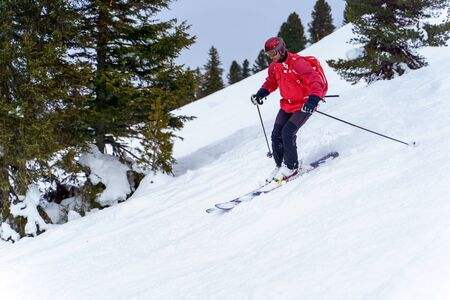 Side photo of sports man in red jacket and with backpack skiing in winter resort from snowy slope with trees