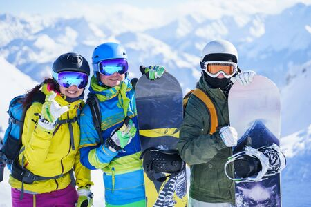Photo of three happy snowboarders in helmet on background of mountains on winter day