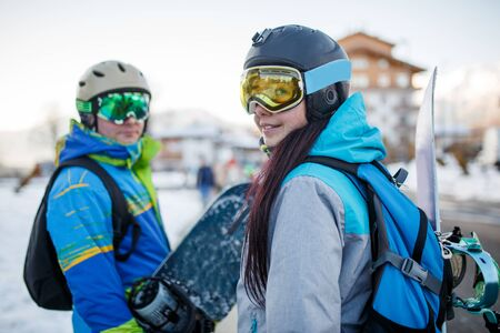 Photo of happy woman in mask with snowboard and men at snow resort in afternoon