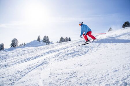 Sportsman in helmet and mask skiing on snowy slope on winter day