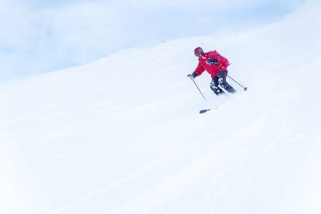Photo of sports man with red backpack skiing in winter resort Reklamní fotografie