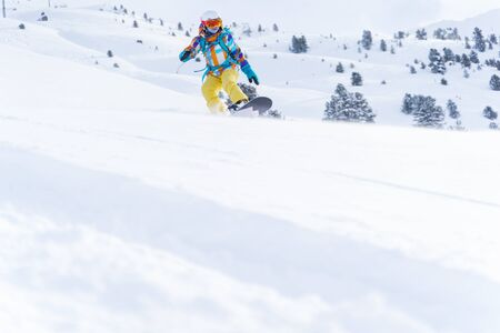 Sports woman in helmet and mask is riding on snowboard on snowy slope at winter day. Photo in full growth. Reklamní fotografie