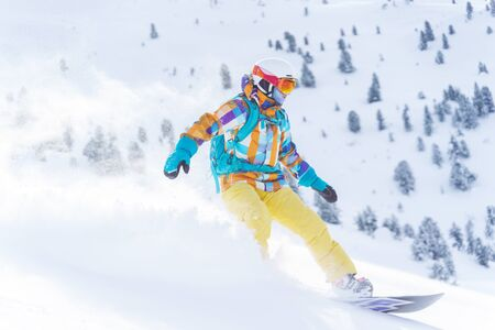 Young sports girl in helmet and mask is riding on snowboard on snowy slope at winter day. Photo in full growth.