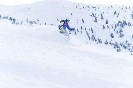 Photo of athlete man in mask and helmet skiing in winter resort on background of hill with trees