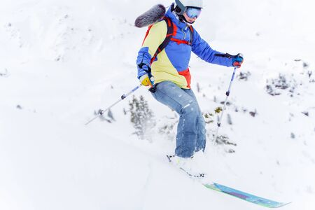 Photo of sports man in multi-colored jacket skiing in winter resort Reklamní fotografie