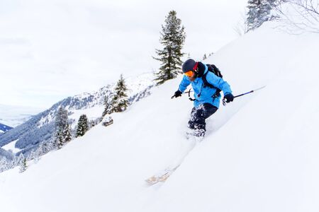 Image of sports man with beard skiing in winter resort from snowy slope