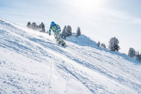 Image of young sportsman in helmet snowboarding at winter resort in afternoon Imagens