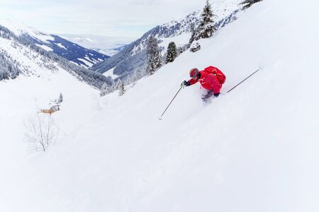 Side photo of athlete man in red jacket and with backpack skiing in winter resort from snowy slope Zdjęcie Seryjne
