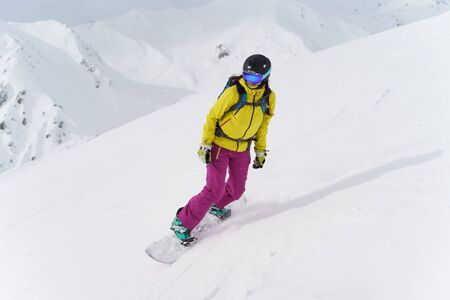 Woman in helmet and mask is riding on snowboard on snowy slope at winter day. Photo in full growth.