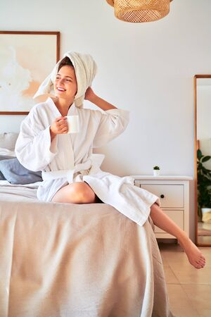 Picture of young girl in white coat with a glass of coffee in her hands lying on bed.