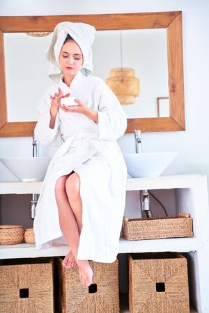 Photo of happy woman with bathrobe with cream in her hands standing in bathroom.