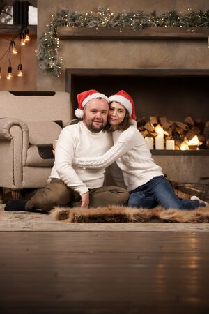 Picture of man and woman in Santas caps sitting on floor in room Stock Photo - 133212198