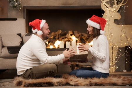 Image from side of man and woman in Santas caps sitting on floor in room Stock Photo - 133212199
