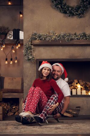 Picture of young couple in Santas caps sitting on sled in room Stock Photo