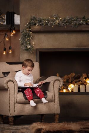 Photo of boy with book sitting in chair in room with New Years interior.