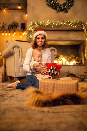 New Years photo of mom in cap of Santa and son with gift sitting on floor.