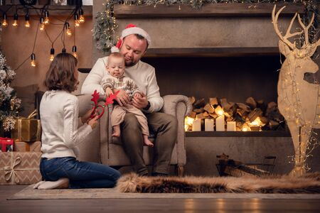 Photo of parents with son at fireplace, deer with garland in room