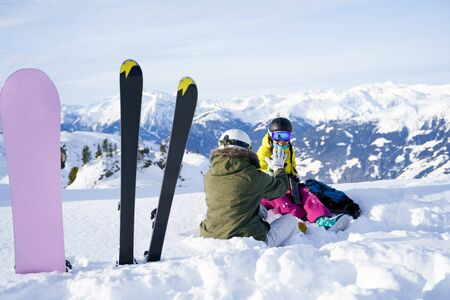 Image from back of two sports women with flask sitting in ski resort in winter in ski resort.