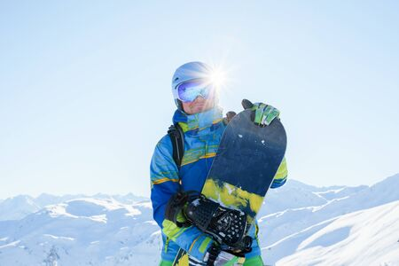 Image of sportsman in blue helmet and goggles with snowboard at ski resort in afternoon. Standard-Bild