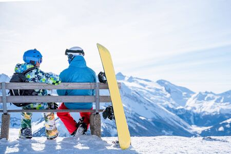 Photo from back of athletes sitting on bench next to snowboard in ski resort