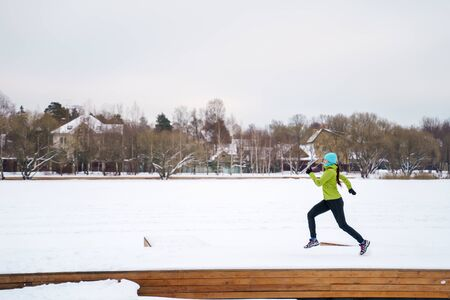 Photo of young athlete running in winter park