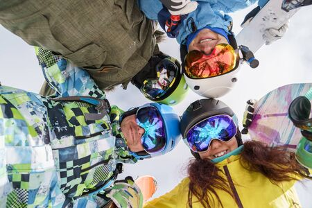 Image of happy snowboarders looking down at winter resort. Photo from below