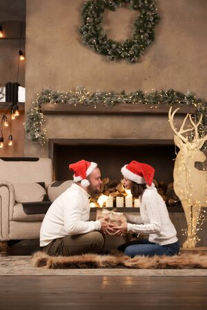 Photo from side of happy man and woman in Santas caps sitting on floor in room