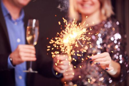 Picture of couple with champagne glasses and sparklers on black background in studio