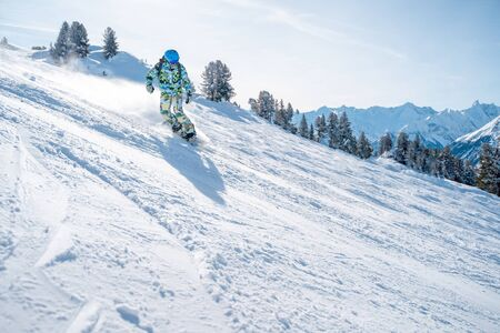 Photo of sports man in helmet with snowboard riding on snowy slope at ski resort