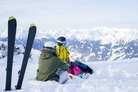 Photo of skis against background of two sports girls sitting in ski resort in winter. Stock Photo