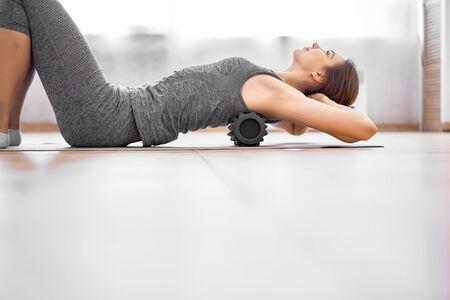 Girl doing yoga lying on massager on grey rug in gym