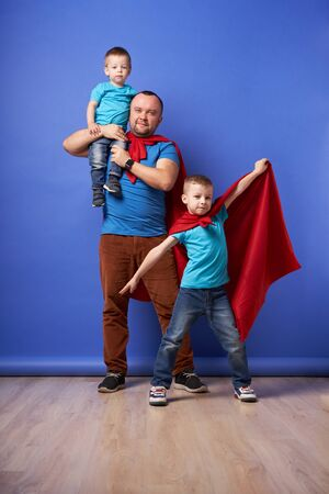 Dad and two sons superheroes in red cloaks on empty blue background