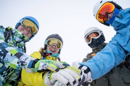Photo from bottom of four happy snowboarders in helmet doing handshake on blue sky.