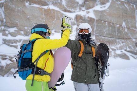 Photo of two sportsmen in helmet and mask doing handshake on background of mountain .