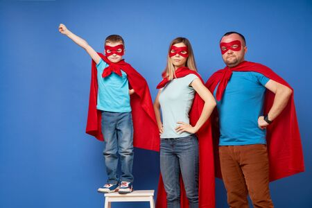 Mom and dad, children superheroes in red cloaks on blank blue background