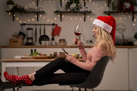 Girl in santa hat with wine glass and phone sits in kitchen with burning garlands. New Years concept
