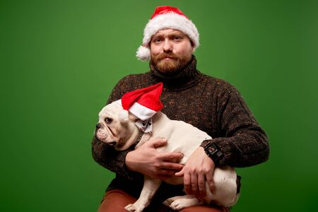 Man and dog in santa caps on empty green background