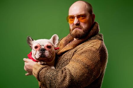 Serious man in glasses with french bulldog in his arms
