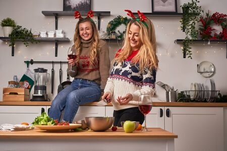 Young women standing in kitchen for christmas.